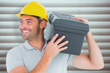 Composite image of handyman carrying toolbox on shoulder