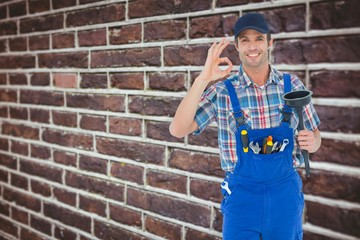 Plumber holding plunger while gesturing ok sign