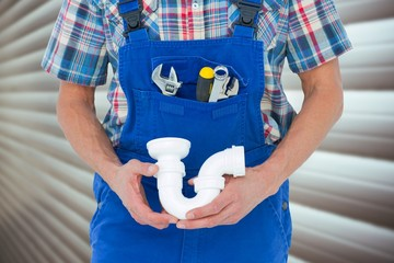 Composite image of cropped image of plumber holding sink pipe