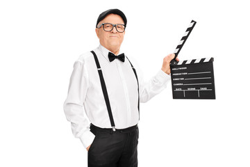 Artistic senior man holding a clapperboard