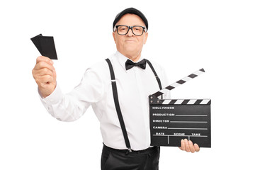 Movie director holding a clapperboard and two tickets