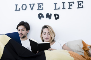 Couple spending a lazy weekend reading book in bed of apartment