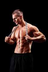 Shirtless young man holding a chain around his neck