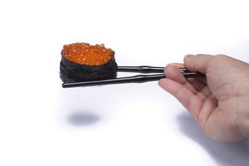 hand holding chopsticks eating sushi om white background