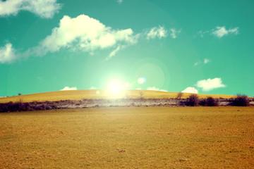 Collina vintage con erba e raggi di sole nel cielo