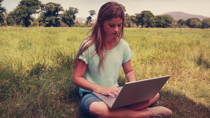 Pretty blonde relaxing in the park with her laptop