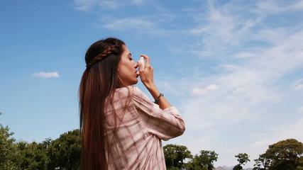 Pretty brunette using her inhaler