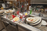 Dirty dishes over flowing in a kitchen sink - 81564840