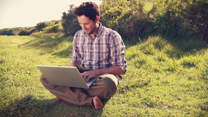 Young man using laptop in the countryside