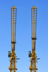 Two construction yellow cranes towers isolated on blue sky