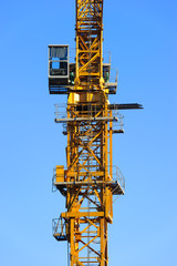 Construction yellow crane tower with operator cabin in blue sky