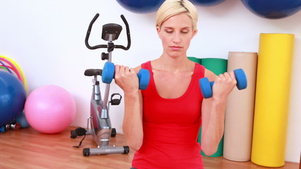 Blonde woman lifting dumbbells on exercise ball