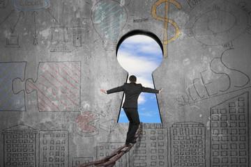 Businessman balancing on iron chain toward keyhole with sky clou