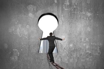 Businessman balancing on iron chain toward keyhole with urban sc