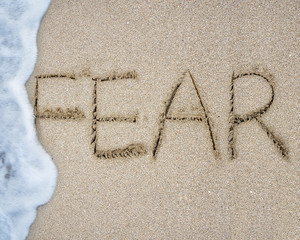 Fear word hand written with wave foam on sand beach