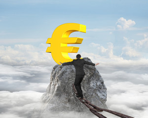 Businessman walking on iron chain toward euro symbol with clouds