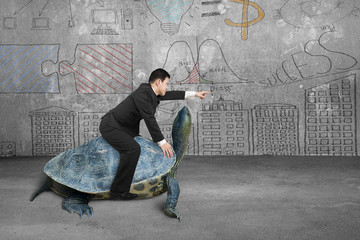 Businessman riding turtle and indicating with finger in concrete