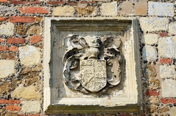 Heraldic stone carving set in wall