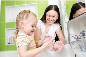 kid girl washing hands with soap in bathroom