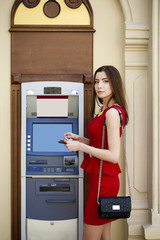Young woman in red dress using an automated teller machine