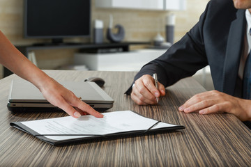 female hand pointing to businessman at signature place on a cont