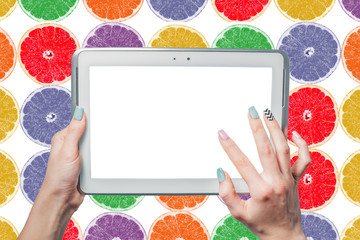 she holds a tablet on a background of citrus