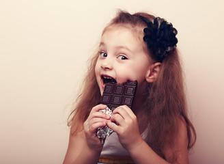 Happy smiling kid girl biting tasty chocolate. Vintage portrait