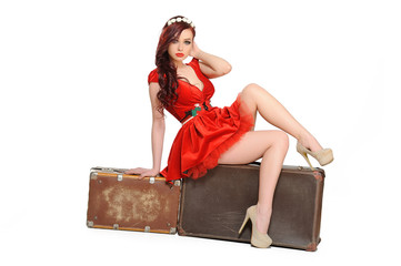 Beautiful woman in a red dress  with retro suitcase