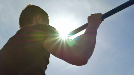 Man pull on the horizontal bar with bright sun background
