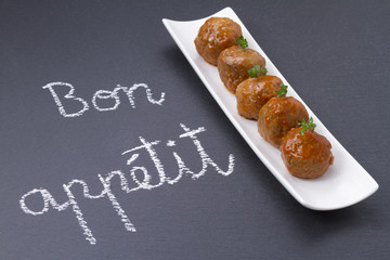 Delicious meatballs. Handwritten message in chalk: Bon appetit