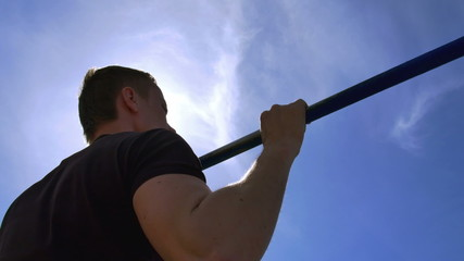 Аthlete pull on the horizontal bar with bright sun background