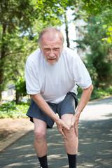 Older man grasping knee in pain