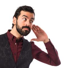 Man wearing waistcoat listening something