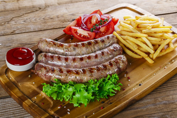 Grilled sausages with french fries on a cutting board