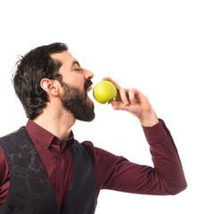 Man wearing waistcoat eating an apple
