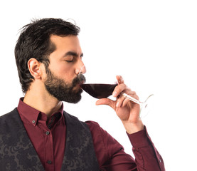 Man wearing waistcoat drinking wine