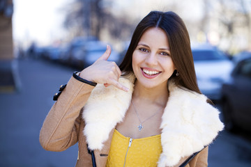 Beautiful happy brunette woman making a call me gesture