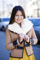 Happy young girl in sheepskin coat on a background of the city