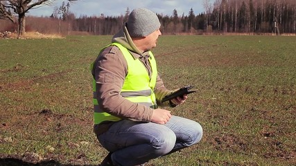 Farmer with tablet PC on the sown field