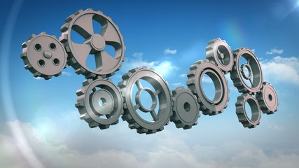 Cogs and wheels turning against blue sky