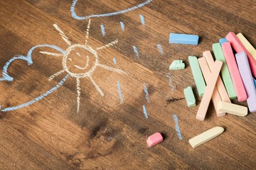 Play. Child's drawings and colored chalk on wooden background