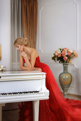 Woman in red long dress leaning over white piano