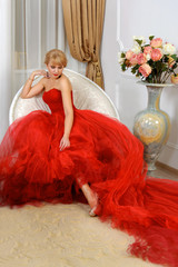 Woman in a red evening gown sits in a chair