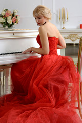 Woman in a red dress playing on a piano