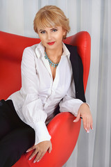 Business woman is sitting in a red chair