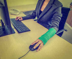 Injured businesswoman hand  clicking computer mouse and typing o
