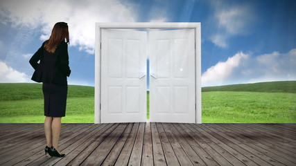 Door opening to green meadow watched by businesswoman