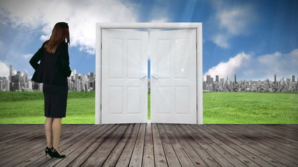 Door opening to city watched by businesswoman