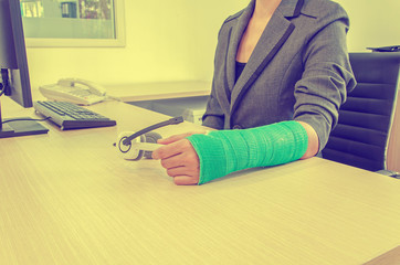 Injured businesswoman with green cast on the wrist holding white