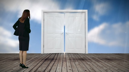 Door opening to blue sky watched by businesswoman